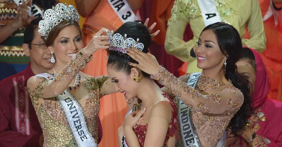 30.jan.2014 - Elvira Devinamira (centro) é coroada pela Miss Indonésia 2013 Wulandari Herman (direita) e pela Miss Universo 2013 Maria Gabriela Isler (esquerda) durante a final do concurso de beleza que elegeu a Miss Indonésia 2014, em Jacarta