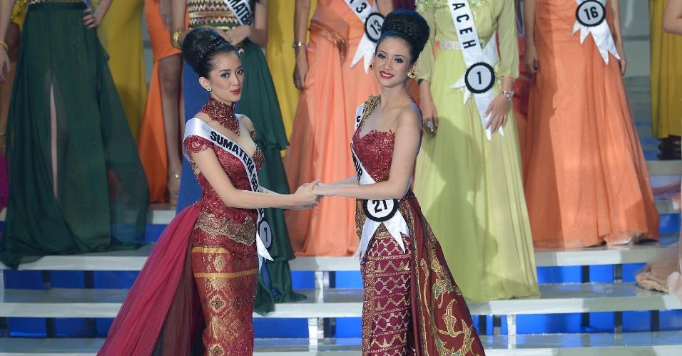 30.jan.2014 - Elvira Devinamira (direita) e Elfin Pertiwi (esquerda) aguardam anúncio do júri sobre quem venceu o Miss Indonésia 2014, cuja final foi realizada em Jacarta