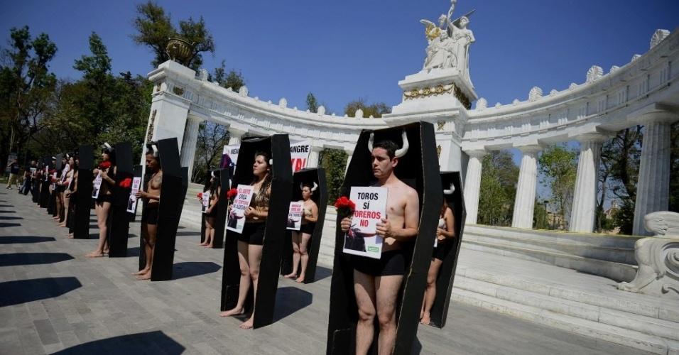 """2.fev.2014 - Membros da organização Anima Naturalis ficam dentro de caixões durante um protesto contra touradas, em frente ao monumento """"Hemiciclo a Juárez"""", na Cidade do México"""
