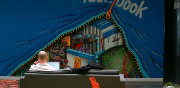 Funcionário do Facebook trabalha com computador em sofá na sede da empresa em Menlo Park, na Califórnia (EUA)