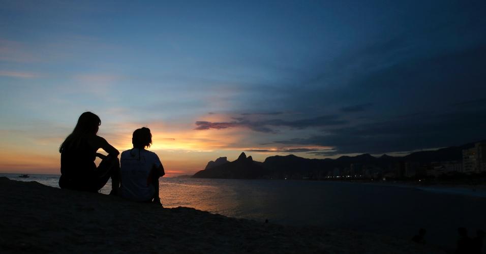 4.fev.2014 - Mulheres observam o pôr do sol na praia do Arpoador, na zona sul do Rio de Janeiro, nesta terça-feira (4), em mais um dia de calor intenso