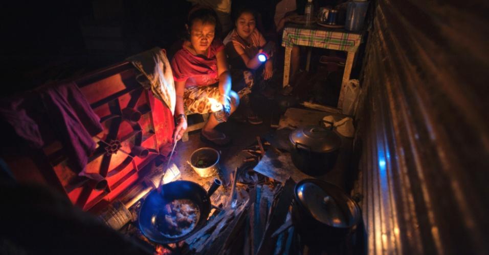 4.fev.2014 - Sobreviventes do tufão Haiyan cozinham com lanterna e luz de lâmpada em Tacloban, nas Filipinas. Quase três meses após a tempestade, a cidade universitária e capital da província, que era próspera, apresenta poucos sinais de recuperação econômica