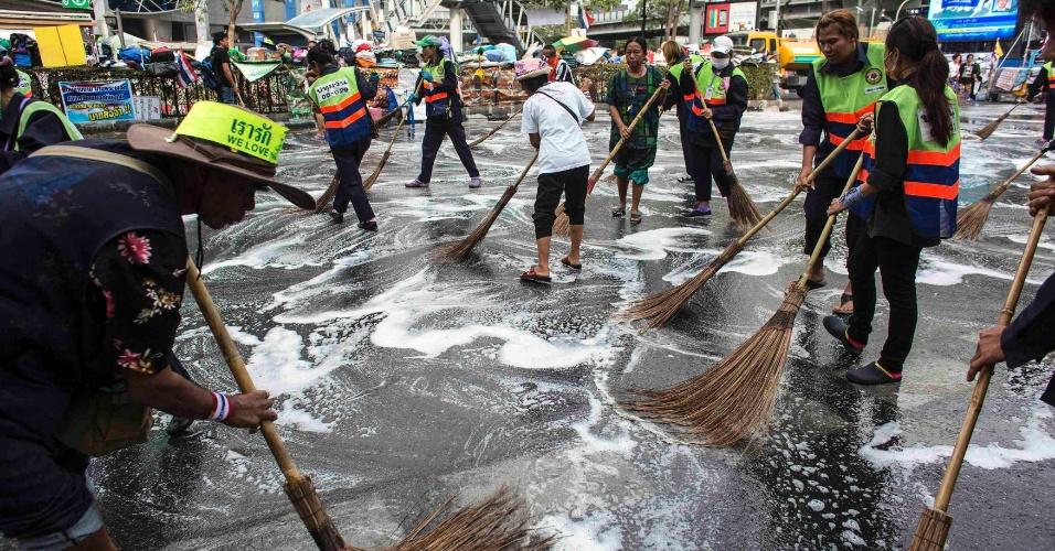 """5.fev.2014 - Funcionários municipais e manifestantes anti-governamentais limpam rua onde os últimos estão acampados no distrito comercial de Bangcoc nesta quarta-feira (5). A oposição tailandesa, que boicotou as eleições antecipadas do fim de semana, apresentaram na terça (4) um recurso na Corte Constitucional do país pedindo a anulação do pleito. Segundo o Partido Democrático, a votação foi uma tentativa do governo da primeira-ministra Yingluck Shinawatra para continuar no poder """"de maneira inconstitucional"""""""