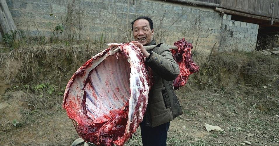 5.fev.2014 - Homem carrega parte da carcaça de uma vaca para um banquete do Ano-Novo chinês na província de Guangxi, na China
