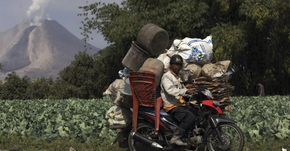 5.fev.2014 - Morador da vila de Simpang Empat carrega seus pertences em uma motocicleta durante evacuação do local provocada pela erupção do vulcão Monte Sinabung