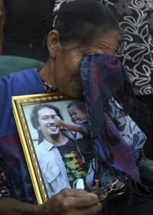 5.fev.2014 - Parentes de Thomas Milala, que morreu durante uma erupção do vulcão Monte Sinabung no último sábado (1), depositam flores e rezam pelas vítimas do vulcão, que já causou a morte de ao menos 15 pessoas na Indonésia