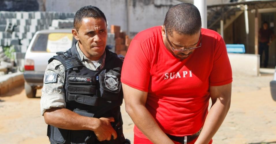5.fev.2014 - Suspeito de ter agredido e mantido a namorada em cárcere privado é conduzido por policial à delegacia de polícia civil em Viçosa (MG) para depor sobre o caso