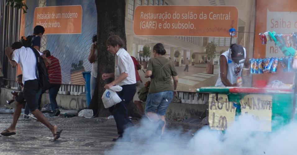 6.fev.2014 - Comerciantes e pedestres correm e buscam proteção contra bombas de efeito moral lançadas pela PM durante confronto com manifestantes que realizavam protesto contra aumento da tarifa de ônibus no Rio de Janeiro