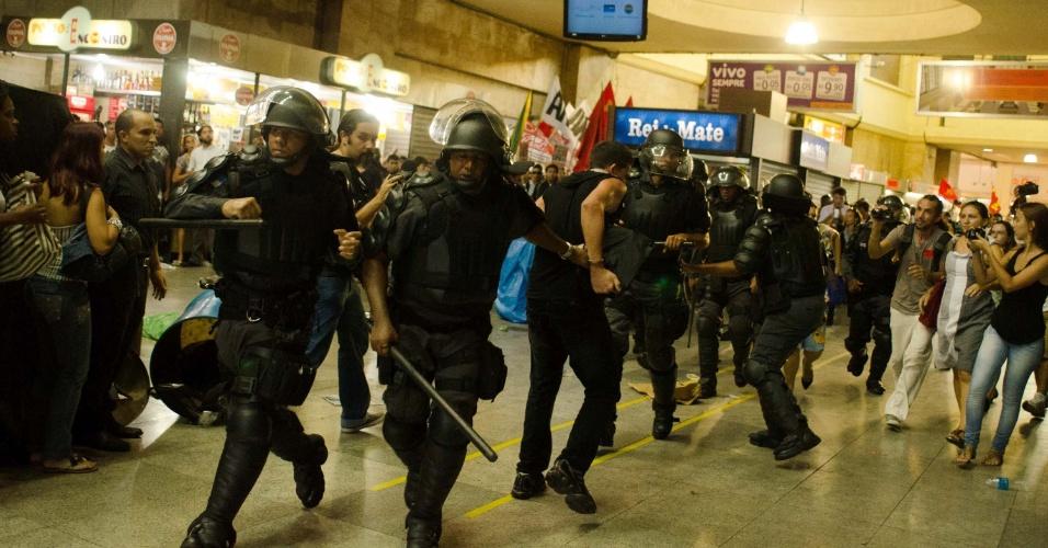 6.fev.2014 - Manifestante é contido por policiais militares durante confronto em protesto contra aumento da tarifa de ônibus na Central do Brasil, Rio de Janeiro