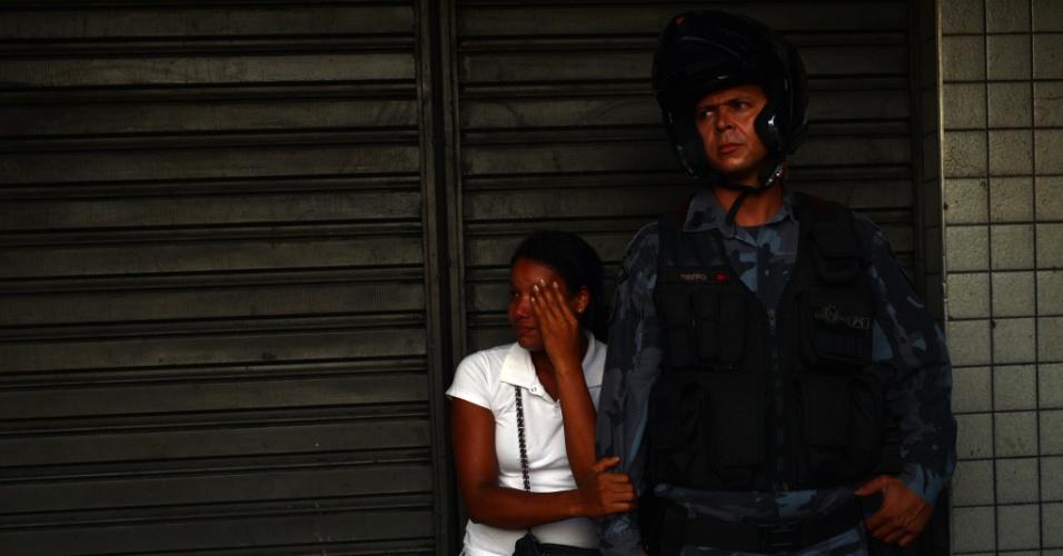 6.fev.2014 - Pedestre assustada com confrontos entre PMs e manifestante em ato contra aumento da tarifa de ônibus no centro do Rio de Janeiro pede proteção a policial