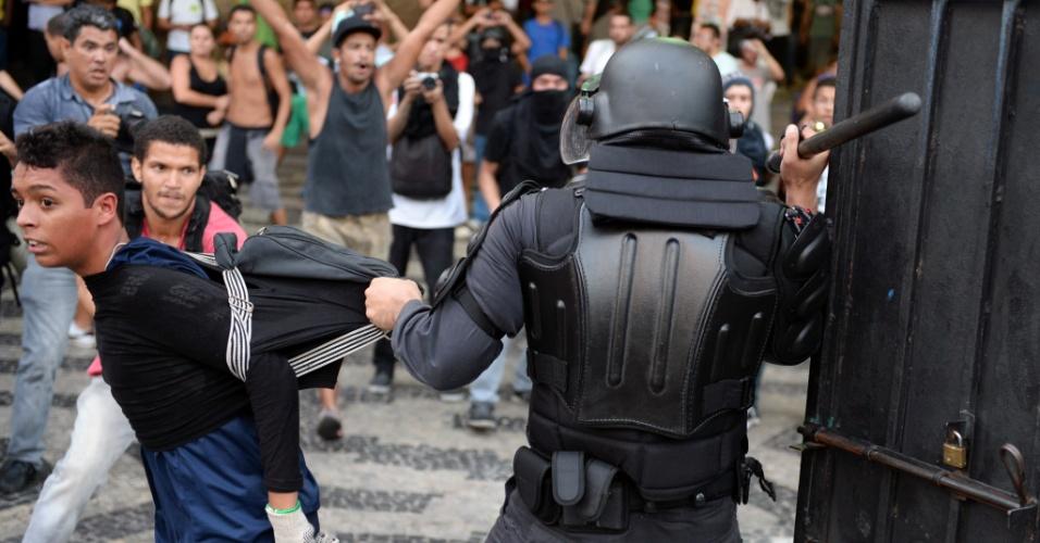 6.fev.2014 - Policial com cassetete em punho contém manifestante durante protesto contra aumento das passagens de ônibus no Rio de Janeiro
