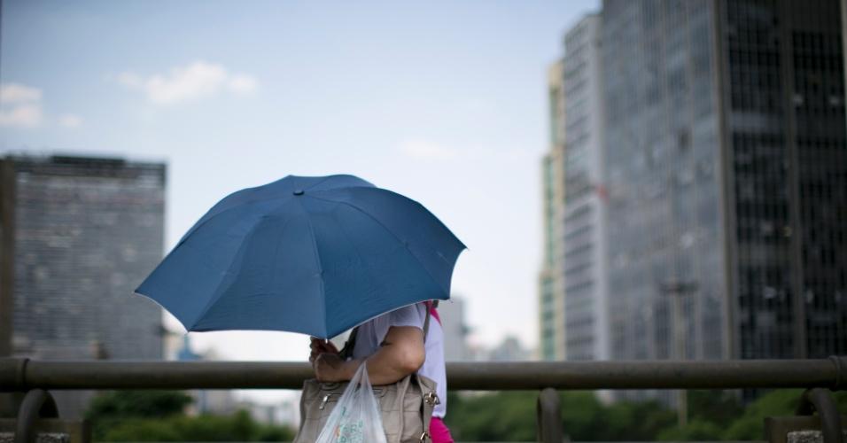 7.fev.2014 - Paulistanos caminhando pelo viaduto do Chá, recorrem a guarda chuva para se protegerem do forte sol que faz na cidade