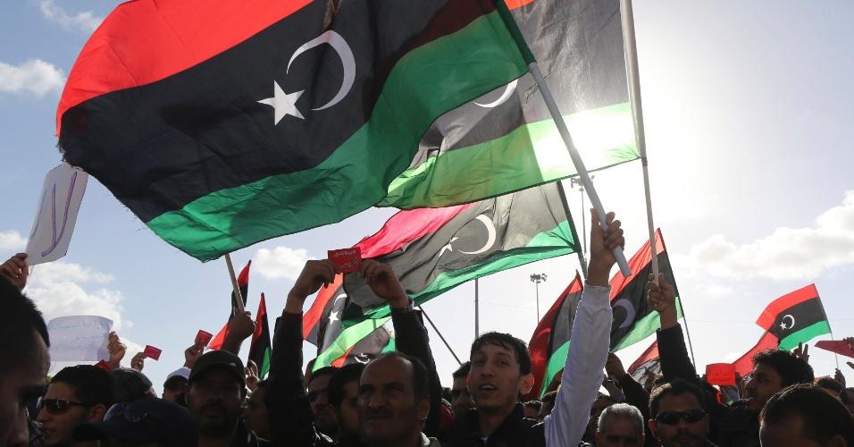 8.fev.2014 - Líbios acenam bandeiras durante manifestação em Benghazi na sexta-feira (7). Milhares de pessoas marcharam naquela cidade e também em em Trípoli para exigir a dissolução do parlamento nacional interino, cujo mandato originalmente deveria expirar ontem