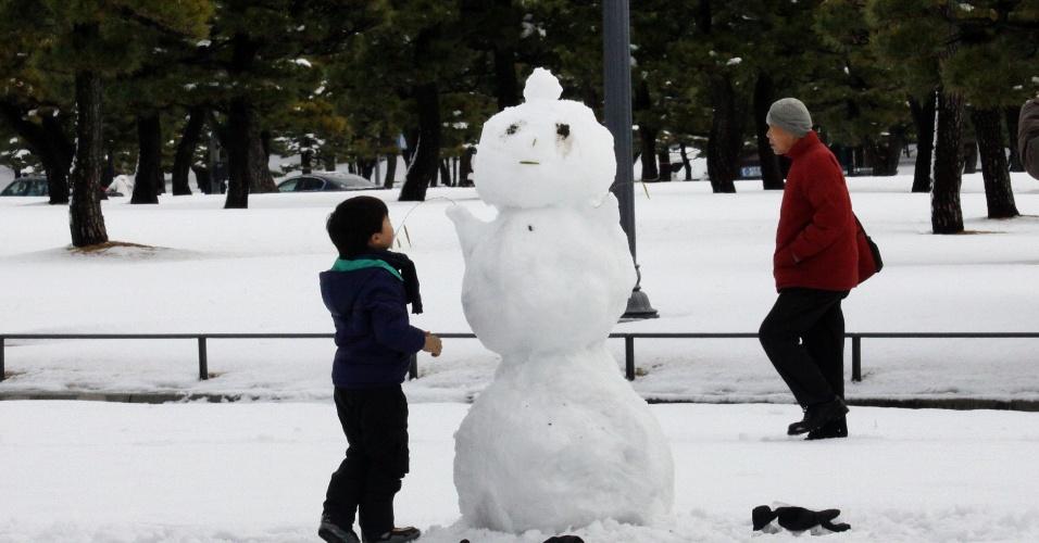 9.fev.2014 - Menina constrói boneco de neve em parque de Tóquio (Japão) após forte nevasca