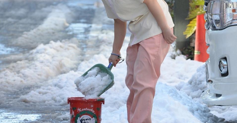 9.fev.2014 - Mulher retira neve de rua em Tóquio (Japão) após forte nevasca