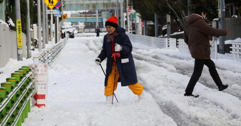 9.fev.2014 - Mulher usa bastões para conseguir cruzar rua coberta de neve em Tóquio (Japão) após forte nevasca