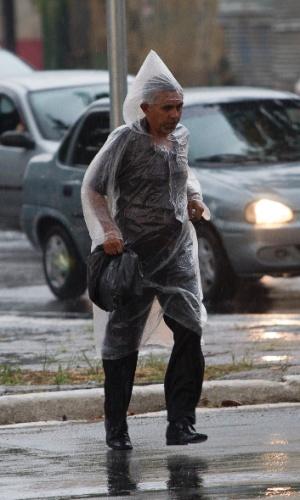 Pedestre usa capa plástica para se proteger da chuva na Barra Funda (zona oeste de São Paulo), no fim da tarde deste domingo (9). O Sistema Cantareira, conjunto de represas que abastece boa parte da capital paulista, atingiu seu menor nível desde 1974, quando foi criado