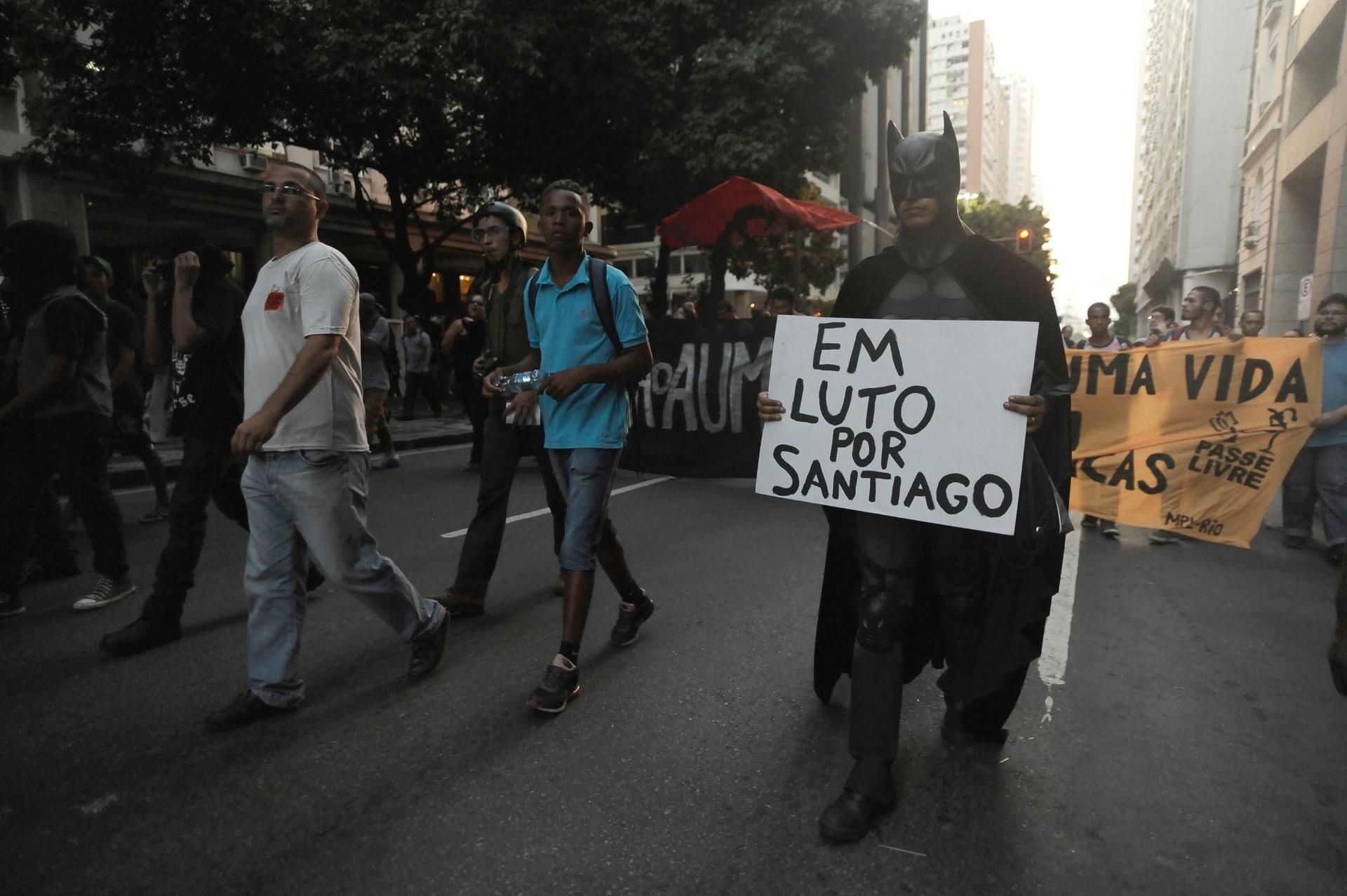 10.fev.2014 - Durante protesto no centro do Rio de Janeiro, Batman segura cartaz em memória ao cinegrafista da TV Bandeirantes, Santiago Ilídio Andrade, que teve morte cerebral após ser atingido por um rojão na última manifestação contra o aumento das passagens de ônibus no Rio de Janeiro