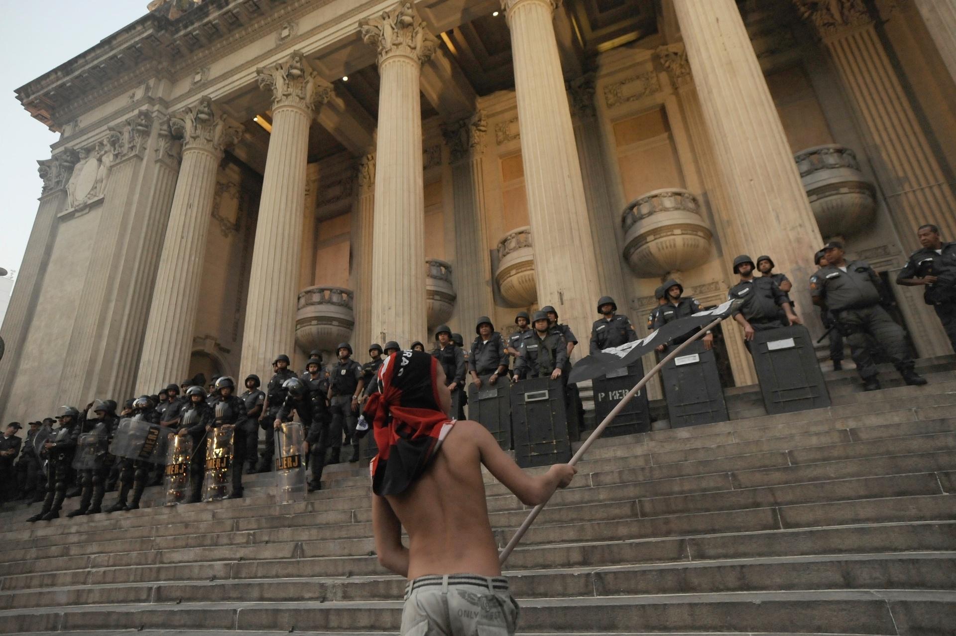 10.fev.2014 - Manifestante ergue bandeira em frente à barreira por policiais militares durante protesto contra aumento das passagens de ônibus, no centro do Rio de Janeiro, nesta segunda-feira (10)