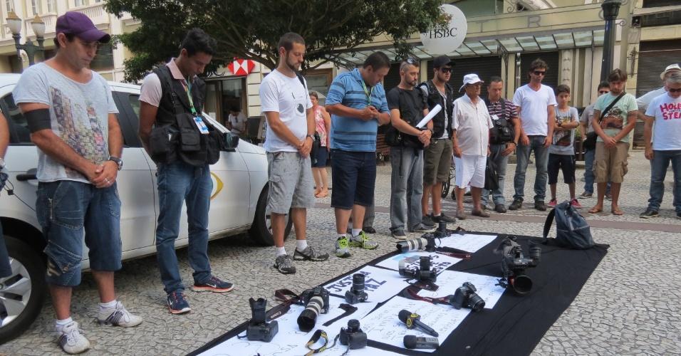 """11.fev.2014 - Jornalistas, cinegrafistas e fotógrafos de Curitiba (PR) colocam equipamentos no chão e fazem um minuto de silêncio, na Boca Maldita (centro da cidade), em homagem ao colega Santiago Andrade, da """"TV Bandeirantes"""""""