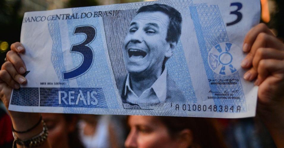 11.fev.2014 - Jovem exibe cédula falsa de real pintada com rosto do prefeito do Rio de Janeiro, Eduardo Paes (PMDB), durante protesto contra aumento da tarifa de ônibus, na capital