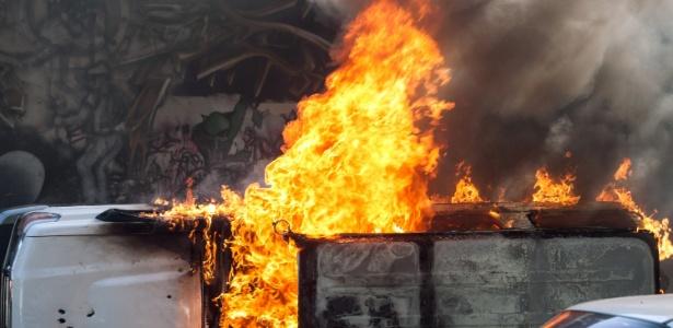 Carro é consumido por chamas após ser incendiado durante protesto em Caracas - Boris Vergara/Xinhua