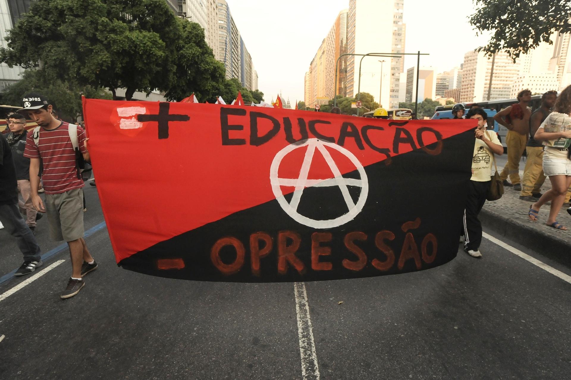 13.fev.2014 - Manifestantes exibem faixas com mensagens de protesto no centro do Rio de Janeiro, durante novo ato contra o aumento das passagens de ônibus