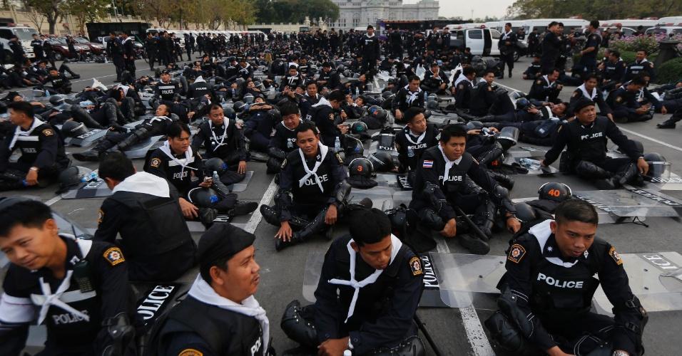 14.fev.2014 - Tropa de choquedescansa na Praça Real, antes de agir sobre acampamento  contra o governo, perto do Palácio do Governo, no centro de Bancoc, nesta sexta-feira (14). Milhares de policiais das tropas de choque foram enviados para tomar de volta locais de protesto em torno de prédios do governo em Bancoc ocupados por meses por manifestantes que procuram derrubar a primeira-ministra, Yingluck Shinawatra