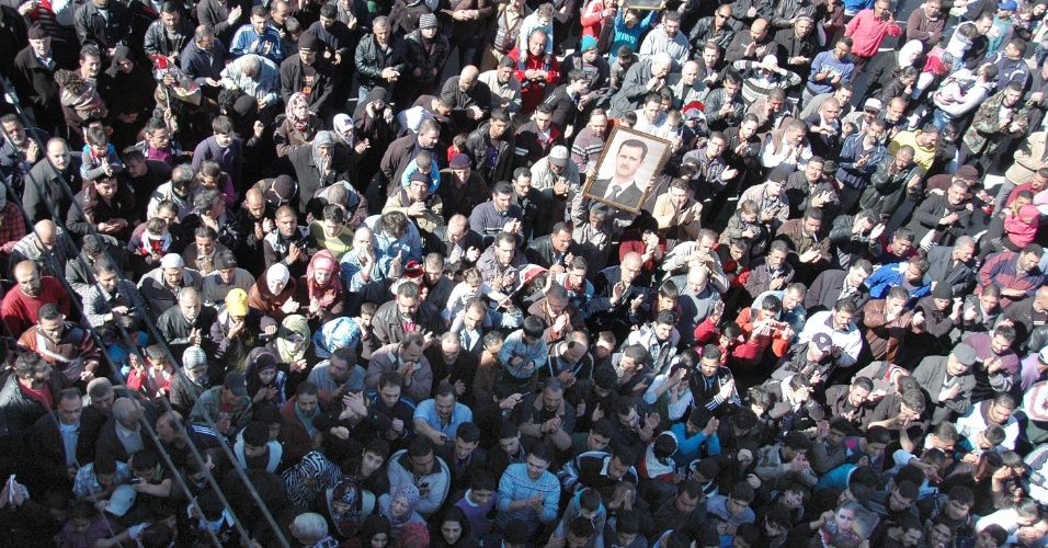 14.fev.2014 - Em imagem divulgada pela agência oficial de notícias da Síria nesta sexta-feira (14), supostos moradores do campo de refugiados de Homs participam de passeata em apoio ao ditador sírio Bashar al-Assad, na cidade de Homs, cercada por tropas do governo desde o começo do mês. Países ocidentais advertiram nesta quinta-feira sobre o destino de homens detidos durante a evacuação das áreas controladas pelos rebeldes da cidade'