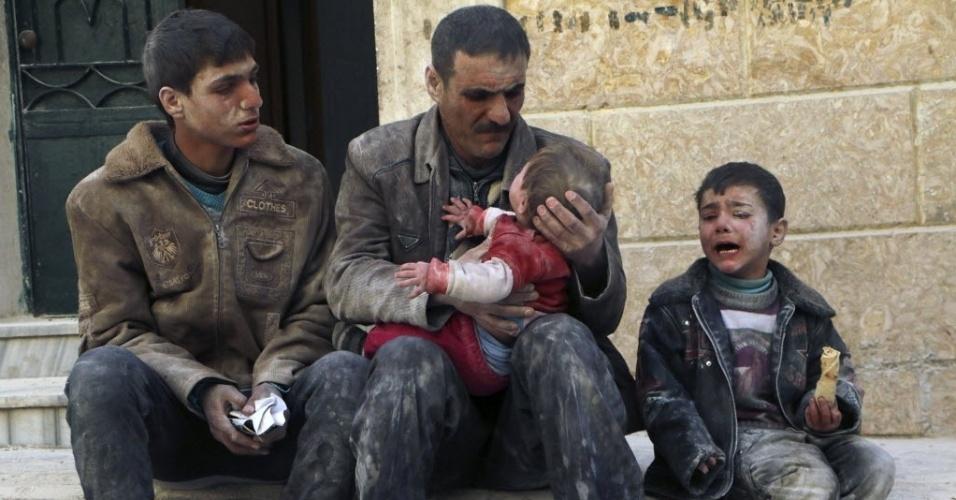 14.fev.2014 - Homem segura bebê resgatado de escombros em prédio atingido por ataque aéreo de forças governamentais da Síria, em Aleppo, nesta sexta-feira (14)