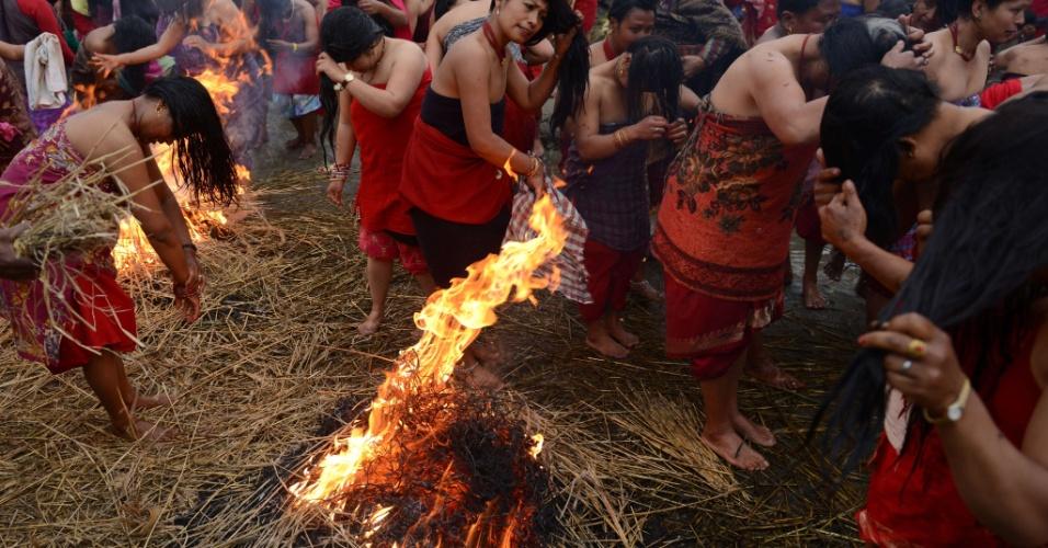 14.fev.2014 - Mulheres hindus do Nepal se aquecem a fogueiras após banho ritual no último dia do festival Swasthani, no rio Hanumante, nos arredores de Kathmandu. A conclusão do festival religioso que durou um mês contou, nesta sexta-feira (14), com dezenas de mulheres submetidas a um jejum, na esperança de uma vida próspera e felicidade conjugal, e um banho no rio, com temperaturas próximas de 10ºC