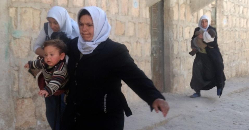 14.fev.2014 - Mulheres sírias carregam crianças enquanto fogem de ataque aéreo das forças governamentais na cidade de Aleppo. Mais de 136 mil pessoas morreram e milhões tiveram que deixar suas casas durante os quase três anos de guerra civil no país
