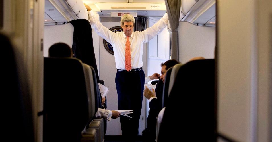 14.fev.2014 - O secretário de Estado dos EUA, John Kerry, fala com sua equipe durante voo de Seul a Pequim, nesta sexta-feira (14)