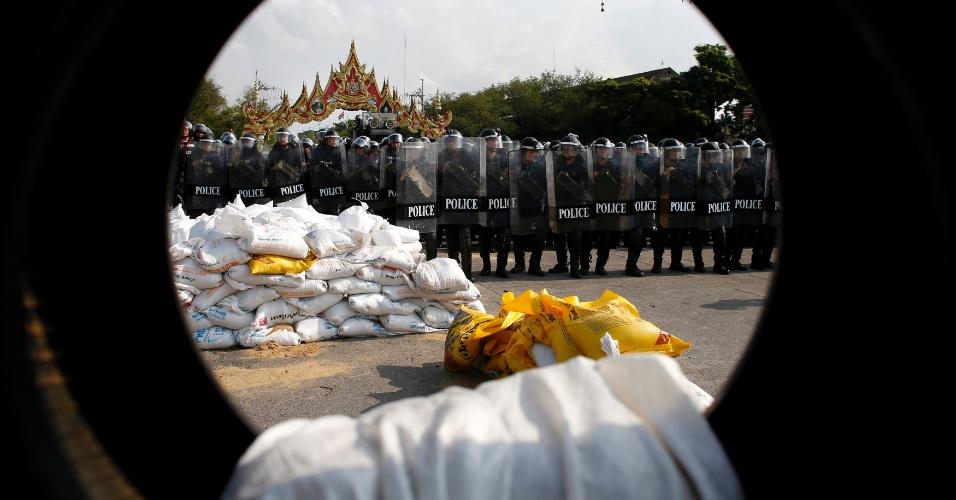 14.fev.2014 - Policiais tailandeses formam linha na frente de protesto diante do palácio do governo, em Bancoc, nesta sexta-feira (14). Milhares de policiais das tropas de choque foram enviados para tomar de volta locais de protesto em torno de prédios do governo em Bancoc ocupados por meses por manifestantes que procuram derrubar a primeira-ministra, Yingluck Shinawatra