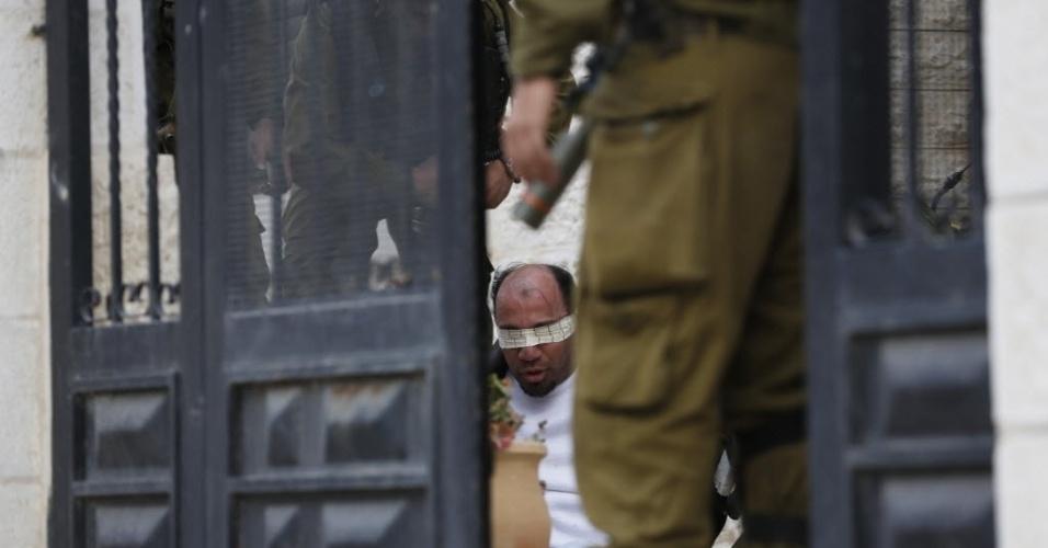 14.fev.2014 - Soldados israelenses vigiam palestino detido durante confronto em uma manifestação contra o assentamento judaico de Beit El, no campo de refugiados de Jalazoun, próximo a Ramallah