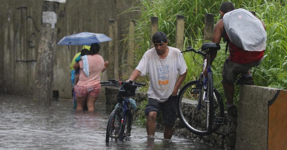 15.fev.2014 - Homens carregam bicicletas em meio a um alagamento na passagem que dá acesso do Parque Ecológico do Tietê à avenida Assis Ribeiro, na zona leste de São Paulo (SP), neste sábado (15)
