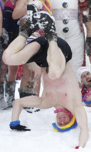 15.fev.2014 - Homem fica de cabeça para baixo durante banho de neve em comemoração ao Carnaval de Inverno em Québec, no Canadá