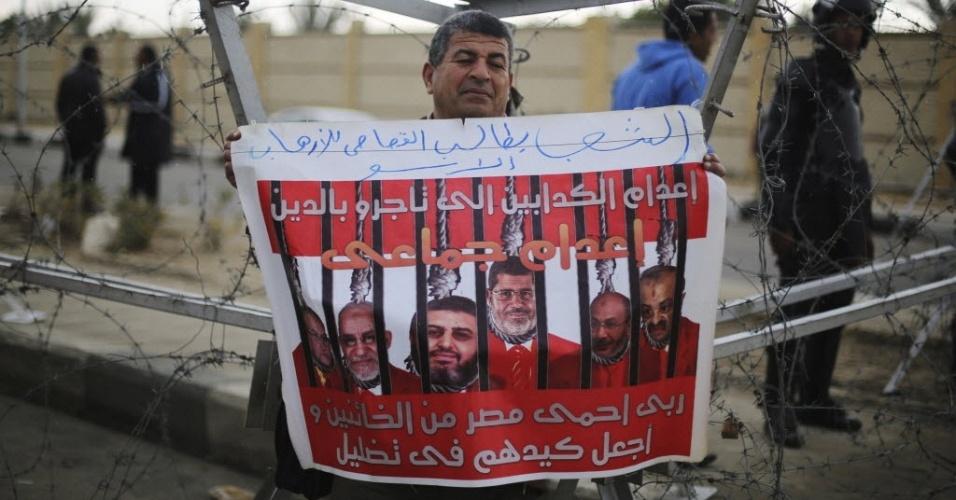 16.fev.2014 - Apoiador das Forças Armadas do Egito mostra cartaz com a foto do presidente deposto Mohamed Mursi e membros da Irmandade Muçulmana atrás das grades, neste domingo (16), na capital Cairo. O julgamento de Mursi, acusado de espionagem, foi suspenso nesta manhã depois que os advogados do presidente deposto abandonaram a sessão