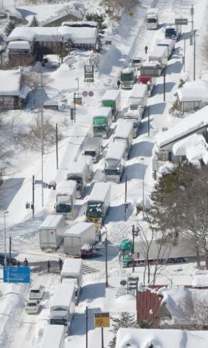 16.fev.2014 - Forte neve impede a passagem de caminhões e carros e geras filas em uma estrada de Karuizawa, no Japão, neste domingo (16). Nevasca que atinge o país já deixou, pelo menos, 11 mortos e várias regiões sem eletricidade