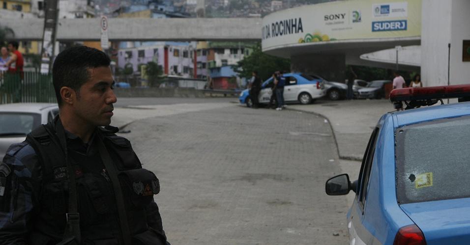 16.fev.2014 - Policial observa carro da PM que foi baleado durante tiroteio entre facções rivais na Rocinha, zona sul do Rio de Janeiro, neste domingo (16). O túnel Zuzu Angel chegou a ser interditado na madrugada de hoje, mas foi posteriormente liberado, segundo a Prefeitura