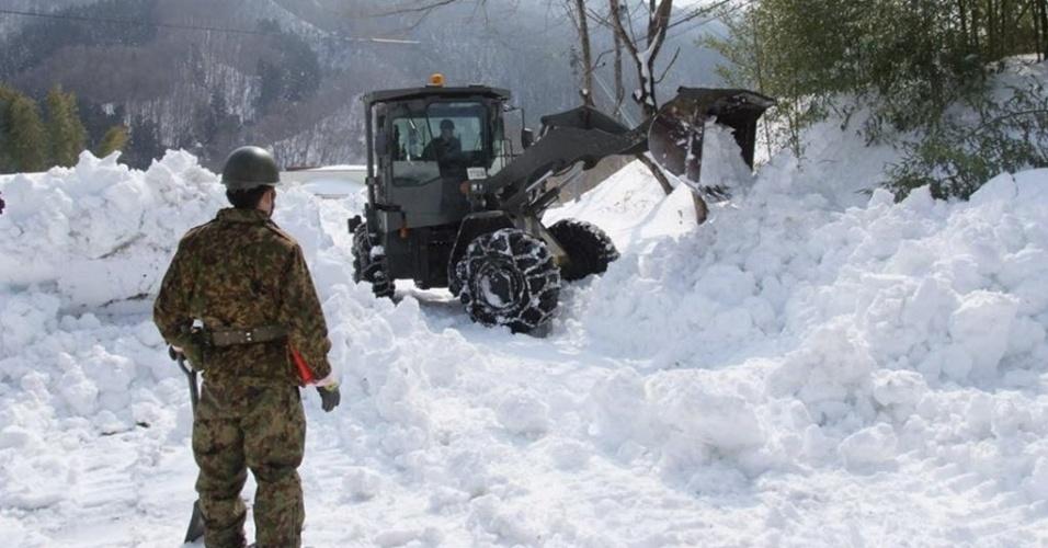 18.fev.2014 - Membro de força de defesa do Japão observa escavadeira remover neve em rodovia da cidade de Marumori. As tempestades de neve no Japão bloquearam diversas estradas em todo o país nesta terça-feira (18). O número de mortes causadas pelo mau tempo subiu para 23