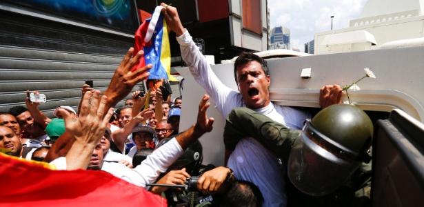 O líder oposicionista da Venezuela Leopoldo Lopez entra em um veículo blindado da Guarda Nacional após ser detido em Caracas nesta terça-feira (18). Ele é acusado de fomentar os protestos violentos no país. Lopez se entregou hoje às forças de segurança - Jorge Silva/Reuters