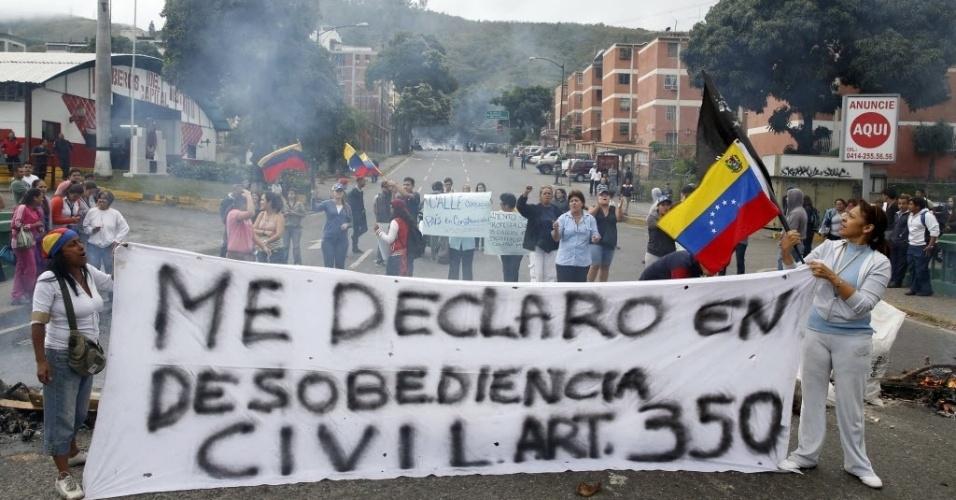 20.fev.2014 - Apoiadores do líder da oposição venezuelana, Leopoldo López, bloqueiam rua durante protesto contra o presidente Nicolás Maduro, em Caracas, nesta quinta-feira (20). Ao menos seis pessoas morreram desde o início dos protestos na semana passada