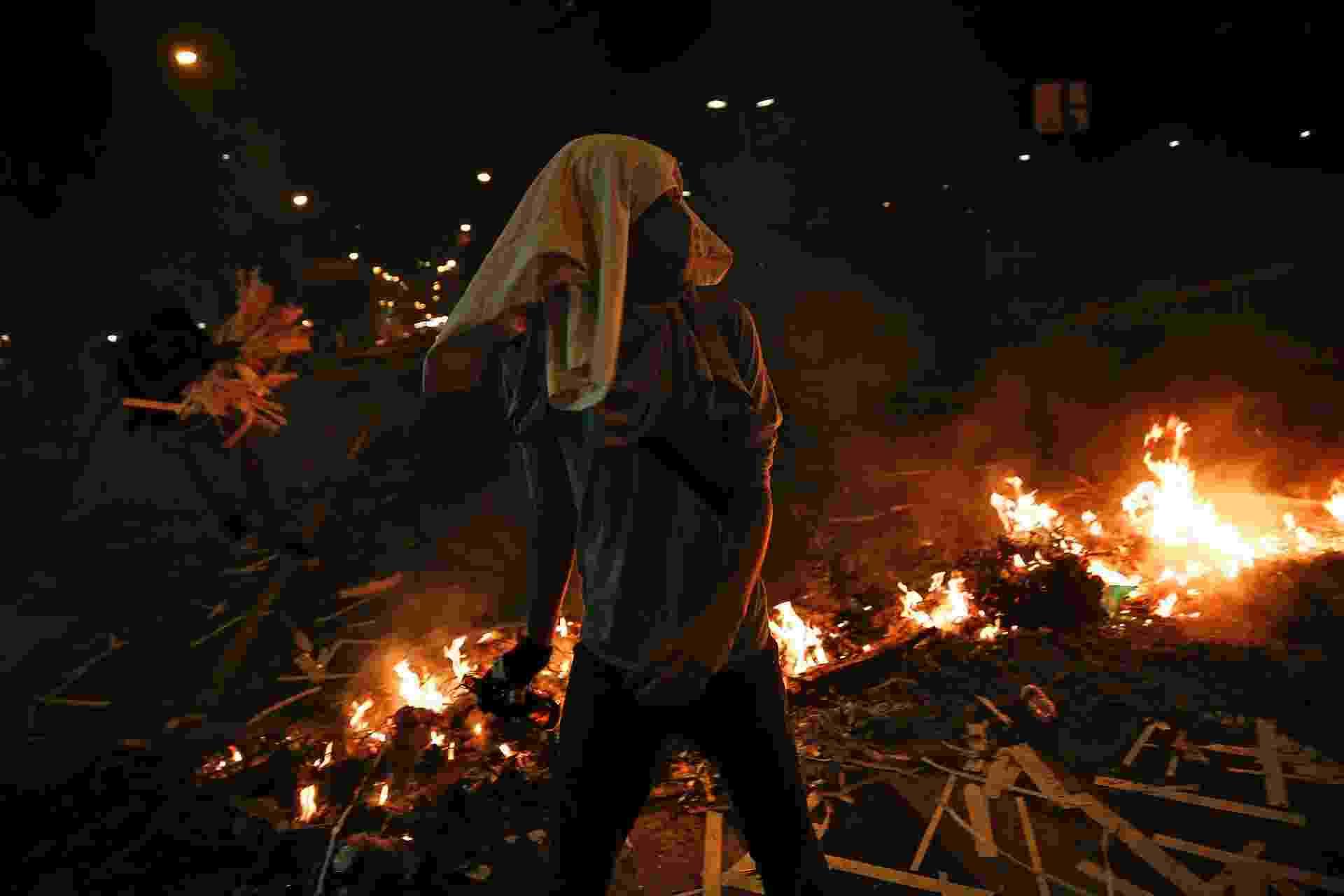 20.fev.2014 - Manifestantes passa por barricada que queima em rua bloqueada na praça Altamira, em Caracas, nesta quinta-feira (20). Forças de segurança da Venezuela e manifestantes se enfrentaram nas ruas bloqueadas por barricadas em chamas em várias cidades provinciais, em protesto contra o governo de Nicolás Maduro - Carlos Garcia Rawlins/Reuters