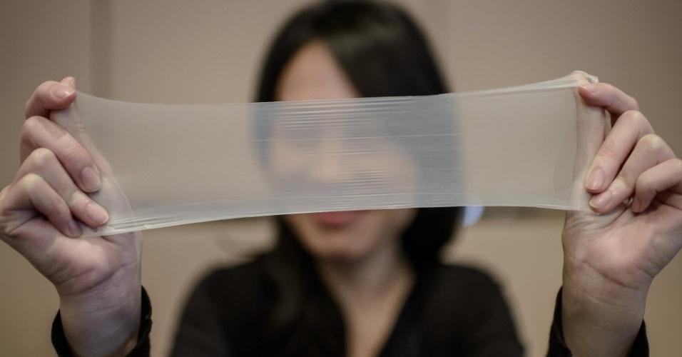 """20.fev.2014 - Mulher alonga um pedaço de látex a partir do qual são feitos os mais finos preservativos do mundo, durante uma conferência de imprensa em Hong Kong, China. Os preservativos fabricados por uma empresa chinesa  entraram para o livro dos recordes como o """"mais fino preservativo de látex"""""""