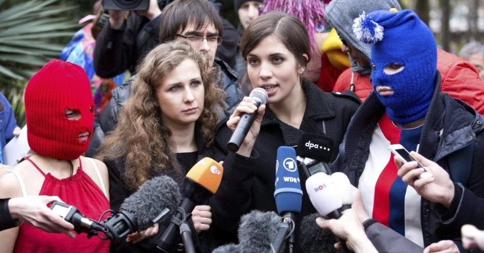 20.fev.2014 - Nadezhda Tolokonnikova e Maria Alyokhina, do grupo punk russo Pussy Riot, e dois ativistas mascarados dão entrevistas para a imprensa na frente das portas de um hotel Sochi, na Rússia, nesta quinta-feira (20)