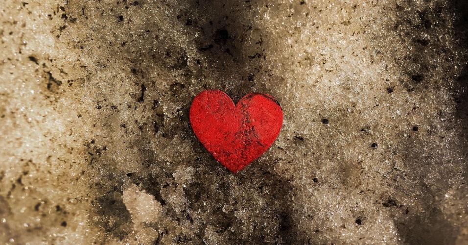 20.fev.2014 - Um coração de papel é visto em cima de um monte de neve derretendo nesta quinta-feira (20), quando as temperaturas de Nova York, nos EUA, começaram a aumentar, revelando lixo que tem sido enterrado por dias de neve e frio
