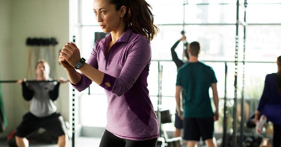 Mulher utiliza o acessório Samsung Gear Fit. Ele é um aparelho que serve para monitorar atividades físicas. O gadget tem uma tela curva de 1,84 polegada e conta com uma série de sensores como pedômetro, medidor de batimento cardíaco e cronômetro