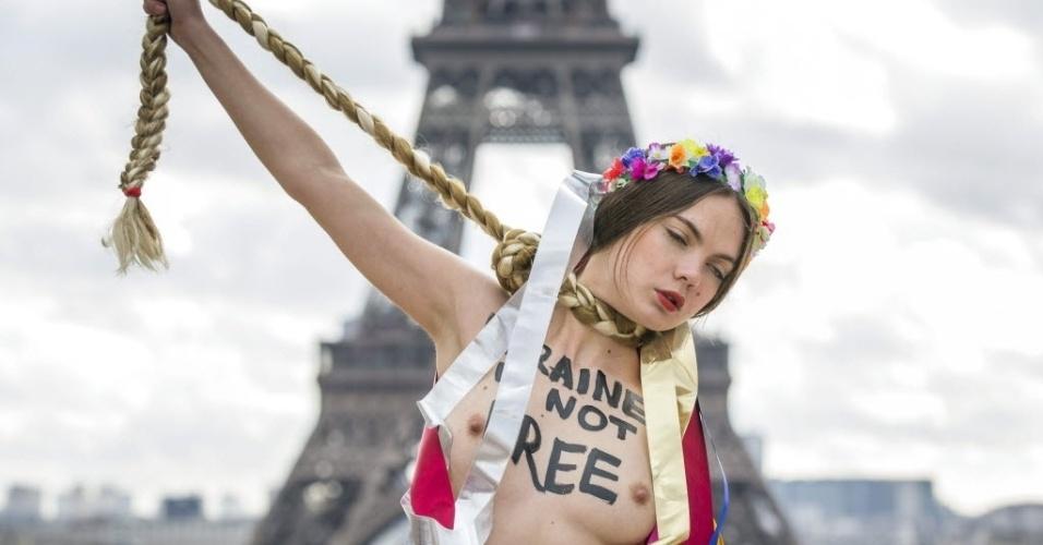 25.fev.2014 - Ativista do grupo Femen protesta contra situação política da Ucrânia e contra a líder da oposição ucraniana, Yulia Timoshenko, em frente à torre Eiffel, em Paris. O Femen classificou a líder da oposição como