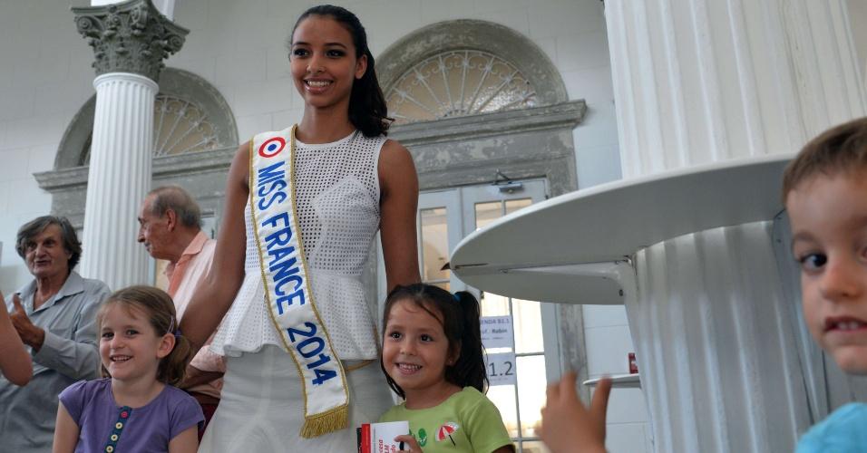 26.fev.2014 - Miss França, Flora Coquerel, posa com crianças durante visita a Aliança Francesa no Panamá